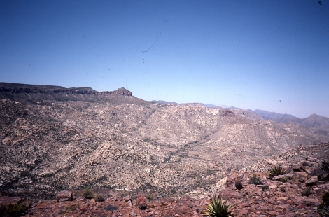 Figure 1.  View to the NW across part of the Main Gulf Escarpment in the southern Sierra San Pedro Mártir of Baja California, Mexico.  Flat-lying mesas (including where the photographer is standing) are the ca. 12.5 Ma Tuff of San Felipe, which is a widespread pyroclastic density current deposit (ignimbrite) found on both sides of the Gulf of California.  Beneath this tuff are, from top to base, deposits of the early to middle Miocene subduction-related volcanic arc; nonvolcanic sedimentary rocks; and Mesozoic tonalites of the Peninsular Ranges Batholith.  Several major E-side-down normal faults offset the volcanic rocks and can be followed as vegetation lineaments within the tonalites.  Photo by the author.