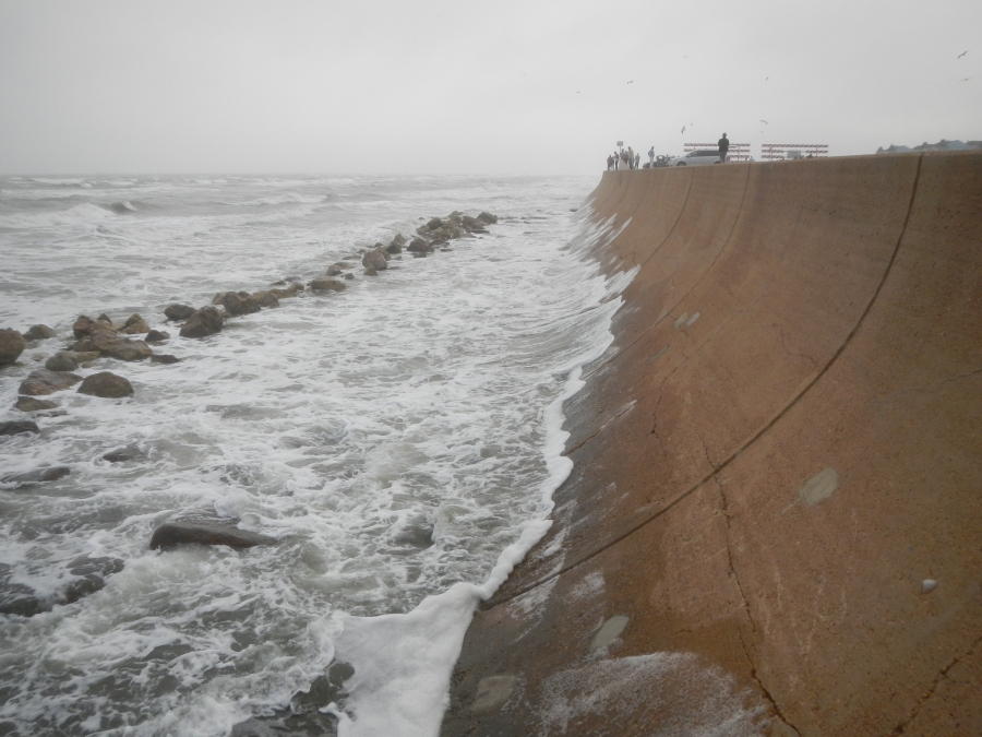 The Galveston Seawall. Note the line of boulders in front of the seawall to dissipate the wave energy before the water washes up the curved surface of the wall.