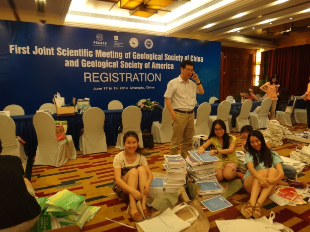 Dr. Shuwen Dong (CAGS) supervising registration matters with Chengdu University of Technology (CDUT) student volunteers.