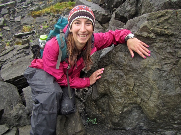 Figure 1: Author Amy Atwater next to a large hadrosaur track in Denali NP.