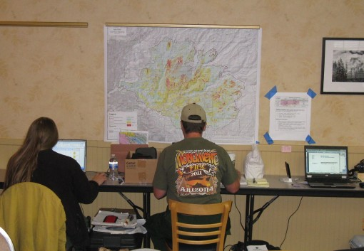Figure 2 – With the soil burn severity map taped to the wall, BAER team specialists use their laptops to model erosion, water flow and other changes due to the effects of the fire on the landscape.