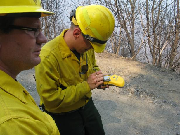 Figure 3 – Electronic note taking devices link field notes to GPS coordinates for later sharing and data manipulation.  The desire for large, more easily read displays is always tempered by how big a device you want to carry in the field.  Geologist Kellen Takanaka enters a note while geotechnical engineer Jonathan Berry looks for the next sample location.