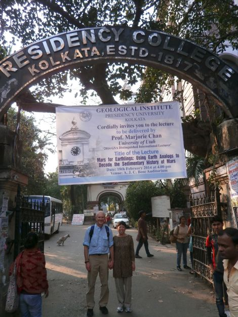 My husband John and I stand at the gate to Presidency University (formerly Presidency College) with a large GSA banner.