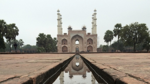 The gate at Emperor Akbar's tomb is reflected in the channel pool of water.