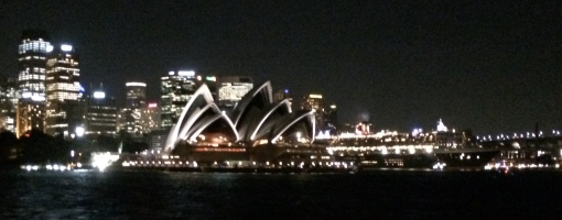 At night, the city lights the harbor and Sydney's opera house.