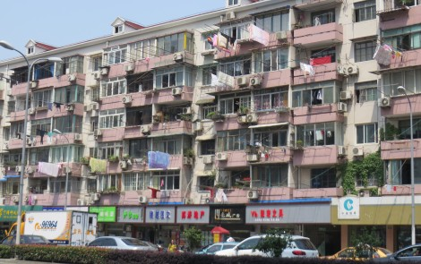 Tall apartment complexes are everywhere and many  have long protruding rods to hang and dry clothes.