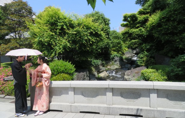 A traditionally dressed couple pauses by the garden waterfall.  Shinoji Temple grounds.