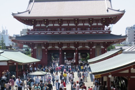 Crowds file through a huge gate into Shinoji Temple, past incense burners.