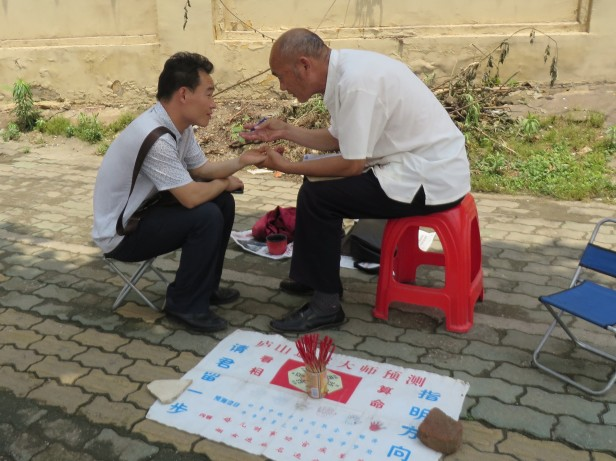 Outside the temple gates, city street fortune tellers read palms and shake sticks.