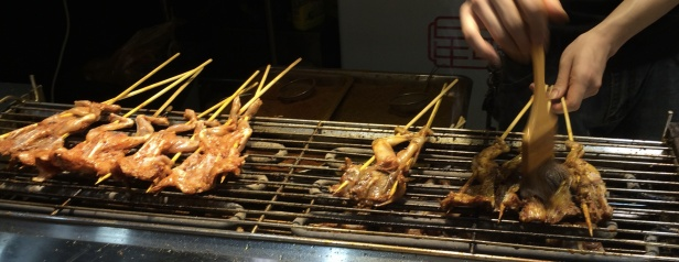 Grilled frogs on a stick are a tasty snack.