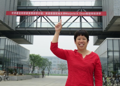 "A large red banner greeted me across the entrance of Yangtze University.  The banner announces part of the ""Plan of World Famous Scientist Lecture- Marjorie Chan"" (approximate translation of Chinese)."
