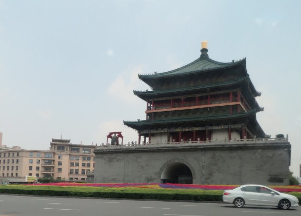 Xi'an's Bell Tower sits surrounded by flowers and a busy traffic circle.