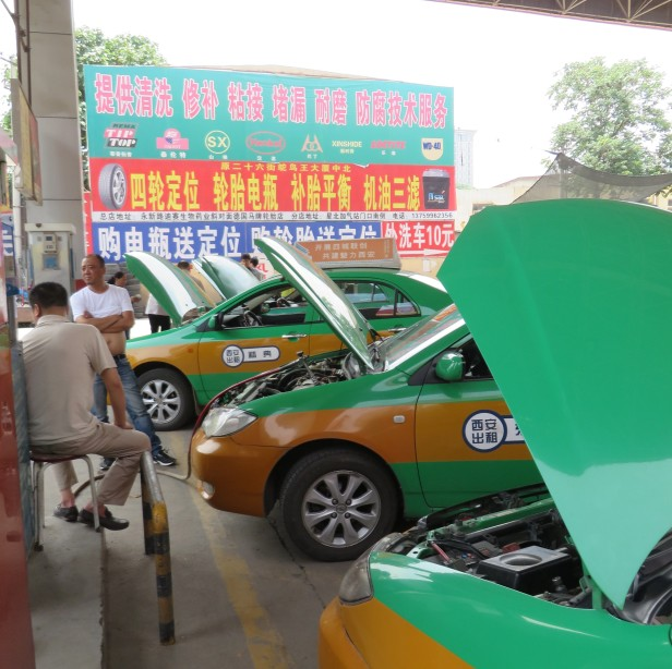 Many taxis have been converted to natural gas, crowd the fueling station and raise their hoods to fill up.
