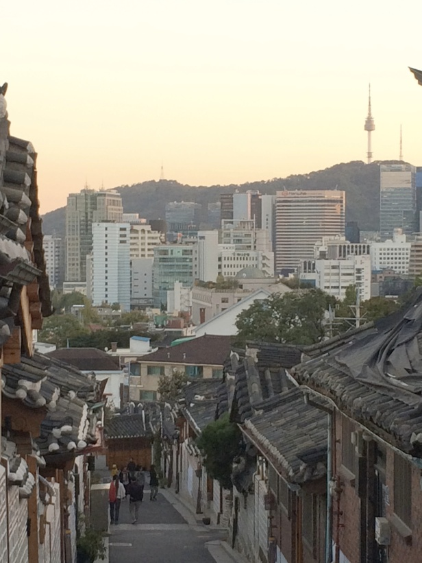 The Bukchon Hanok village has narrow streets and traditional architecture (foreground).  The Seoul Tower is on the right horizon.