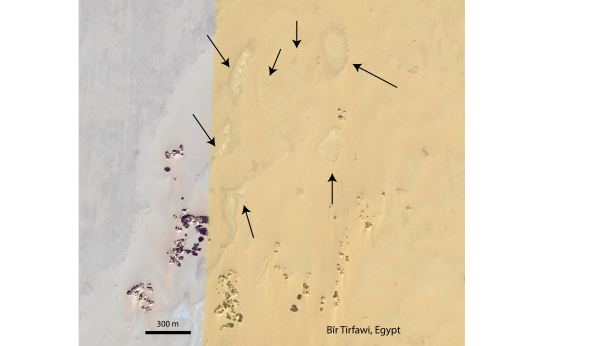 Arrows point to remnant ancient lake deposits visible in aerial imagery, southwest Egypt - Credit: Google Earth