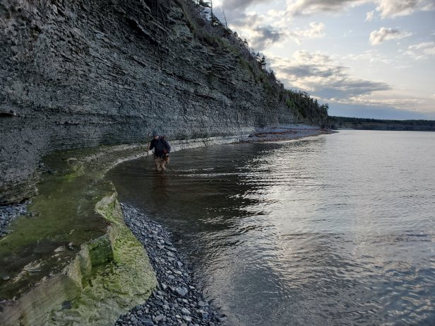 Traversing the Ordovician-Silurian boundary section on the eastern coast of Anticosti Island (Québec, Canada). In this remote location, the fossil and stratigraphic are exposed in towering coastal cliffs that provide continuous access to outcrop.